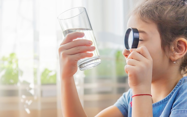 子供はグラスの中の虫眼鏡で水を調べます
