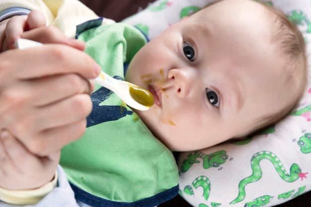 最初のスプーンから餌をやる子供は、初めて野菜を味わう、感情。