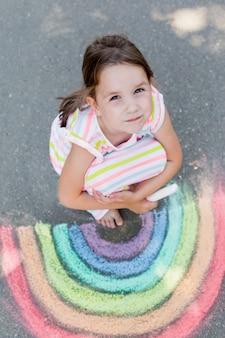 아이 소녀는 아스팔트에 색깔 분필로 무지개를 그립니다. 어린이 그림 그림 개념. 교육과 예술, 학교로 돌아갈 때 창의력을 발휘하십시오