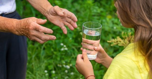 子供は祖母にコップ一杯の水を与えます。セレクティブフォーカス。人。