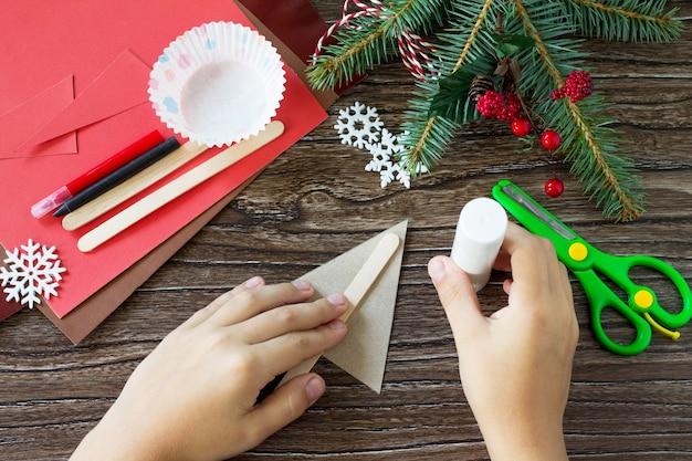 Ребенок склеивает детали рождественские олени куклы ручной работы поделки для детей