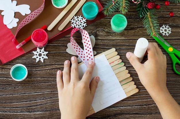Ребёнок склеивает детали дед мороз и оленьи палочки подарок handmade проект детского творчества.