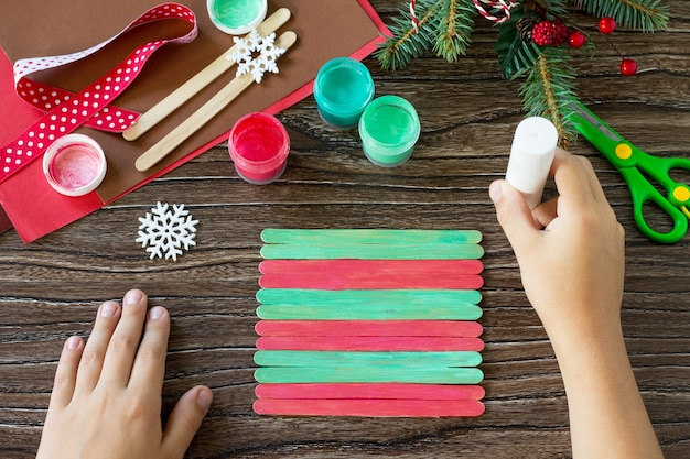Ребёнок склеивает детали палка деда мороза и оленей подарок handmade.