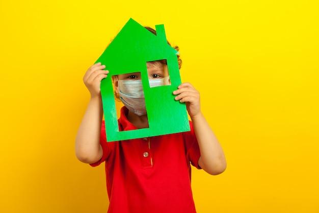 子供は家の中に隠れました。コロナウイルスの検疫。医療用マスクと赤いシャツを着た小さな男の子が、温室のペーパーモデルを手に持っています。黄色の壁に。孤立した