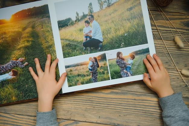 Ребенок держит семейный фотоальбом на деревянном столе