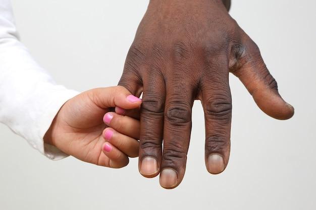 검은 피부의 아버지의 손을 잡고있는 아이