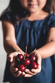 子供はおいしい桜を手に持っています。美しいジューシーなベリー。一握りのサクランボ。ビーガン、エコ、農産物、有機食品