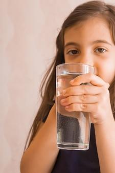 子供はコップ一杯の水を手に持っています。セレクティブフォーカス。