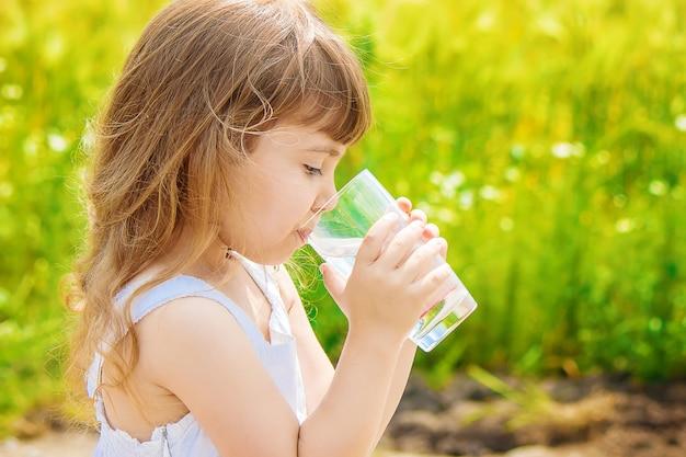 子供は一杯の水を両手に持っています。セレクティブフォーカス