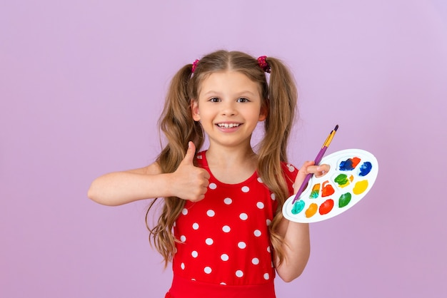 아이는 페인트 팔레트를 들고 엄지손가락을 치켜세웁니다.