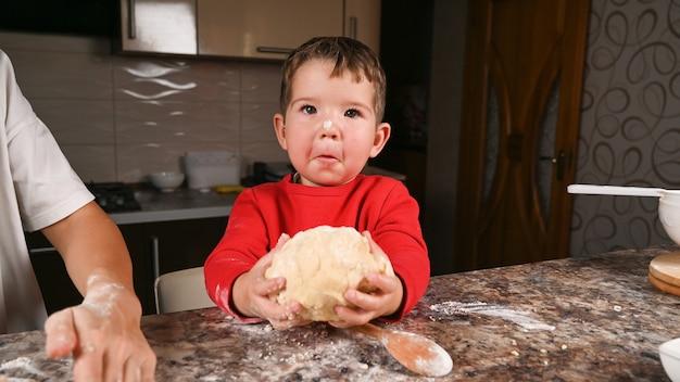 아이는 손에 반죽 조각을 들고 있습니다. 고품질 사진