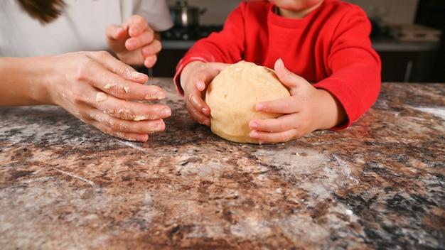 아이는 손에 반죽 조각을 들고
