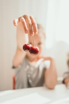 子供は彼の手にさくらんぼを持っています赤とジューシーなさくらんぼのクローズアップぼやけた焦点は子供に