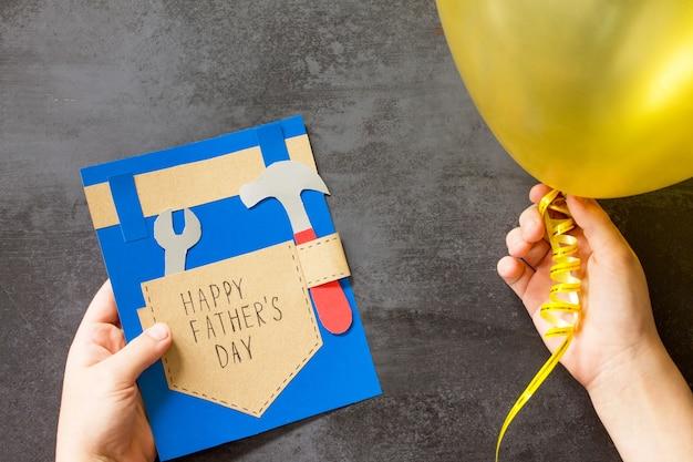 Ребенок держит поздравительную открытку с днем отца.