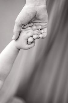 아이는 엄마의 손을 꼭 잡고 있습니다. 그의 어머니와 함께 아이의 흑백 사진. 아이와 부모의 손 클로즈업. 어린 시절에 대한 텍스트를 위한 장소입니다. 고품질 사진