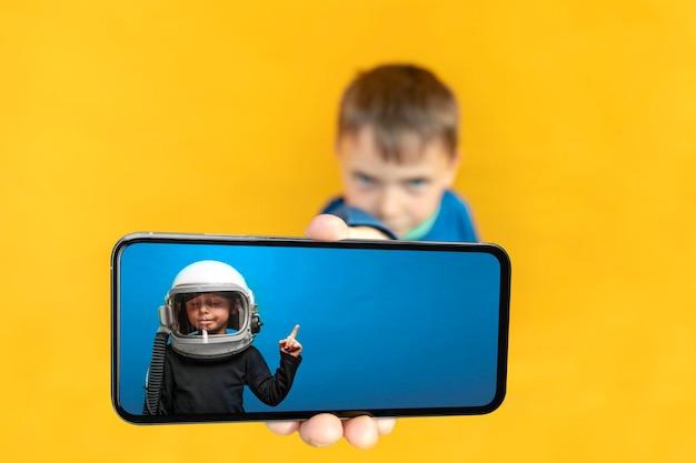 子供は黄色の背景に広告を出すために携帯電話を手に持っています。色