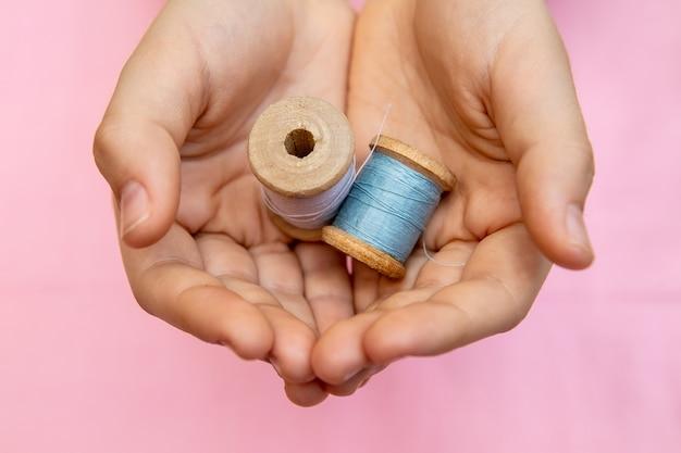 子供は2つの糸のスプールを手に持っています。子供のためのクローズアップ、縫製、裁縫のコンセプト。
