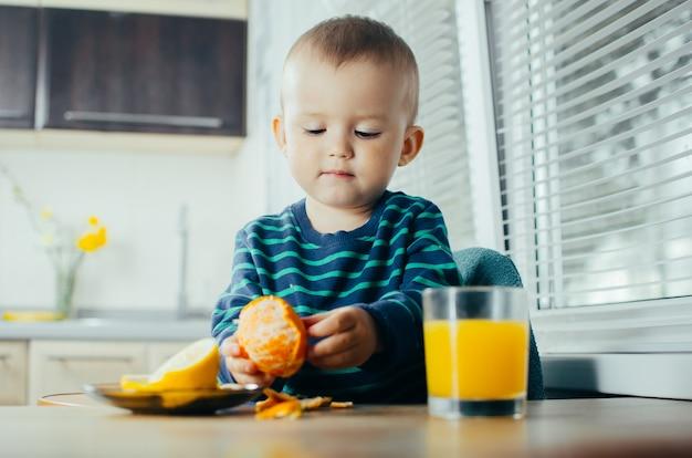 부엌에 있는 아이는 만다린을 청소하고 주스 옆에 서서 그릇에 레몬을 얇게 썬다