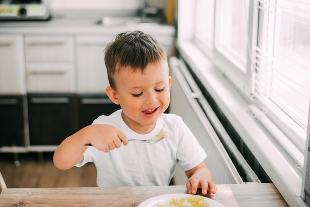 부엌에서 아이가 스스로 소시지와 으깬 감자를 먹고