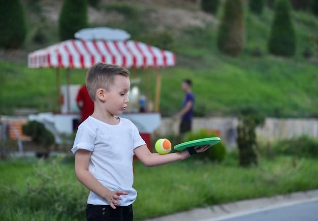 小さなボールと粘着プレートで遊んでいる公園の子供