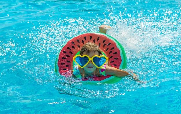 プールの子供は輪になって泳ぎます。セレクティブフォーカス。子供。