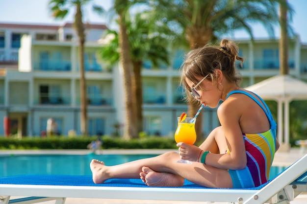 Ребенок пьет коктейль у бассейна