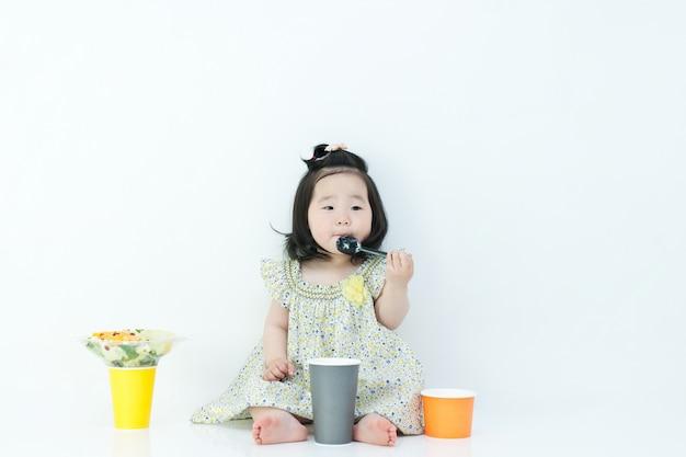 아이가 숟가락으로 이유식을 먹고 있습니다. 입 주위에 이유식이 있습니다.