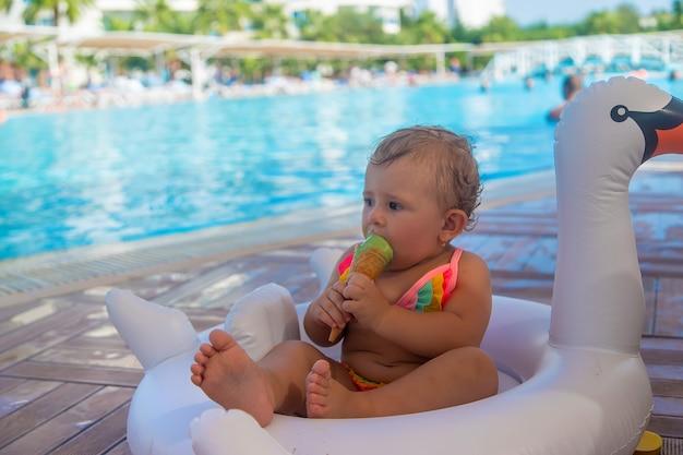아이가 수영장 근처에서 아이스크림을 먹고 있습니다. 선택적 초점입니다.