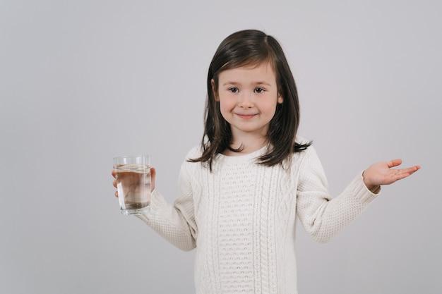 Ребенок держит стакан с водой. девушка хочет пить воду.