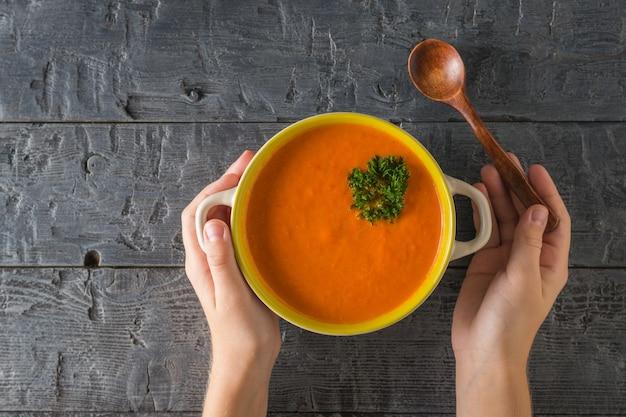 子供は木のテーブルの上に木のスプーンとマッシュポテトのスープを持っています。菜食のスープ。フラットレイ。上からの眺め。