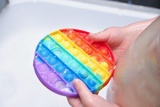 아이가 실리콘 거품이 있는 스트레스 방지 장난감을 들고 욕실에 있는 비누 거품에 팝니다