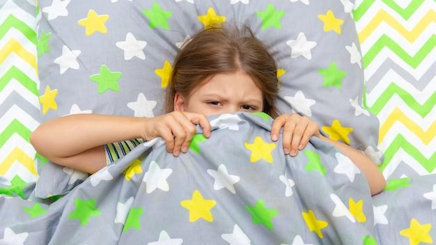 아이는 침대에 누워 있고 일어나서 학교에 가고 싶지 않습니다.