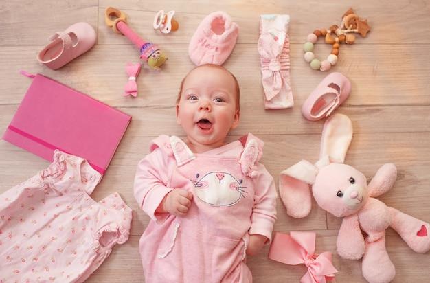 Ребенок лежит на полу среди мягких игрушек и смеется.