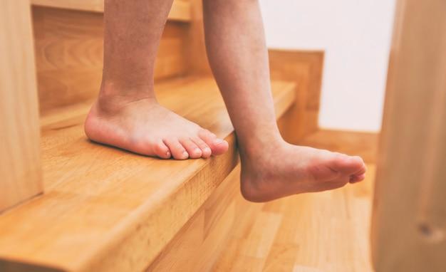 子供は家の木製の階段を通って下に移動しています