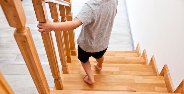 아이가 집의 나무 계단을 통해 아래로 이동하고 있습니다.