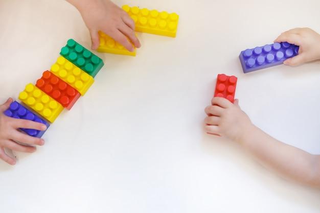 子供はコンストラクタのカラフルな詳細で遊んでいます。手におもちゃ。細かい運動能力、教育ゲーム、子供時代、体外受精、子供の日、幼稚園の発達の概念。コピースペース