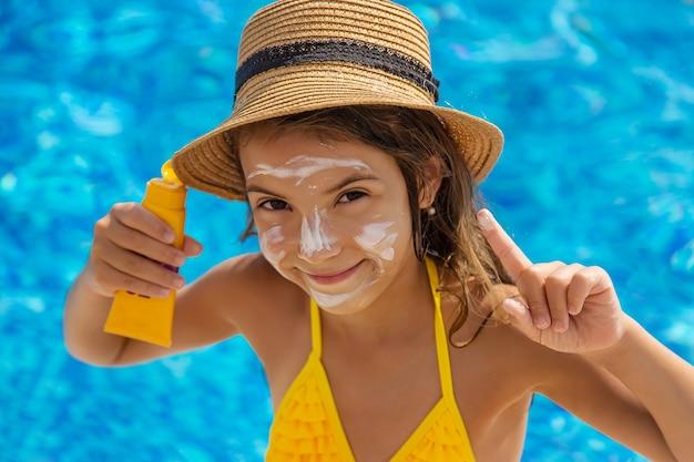 子供は顔に日焼け止めを塗っています。セレクティブフォーカス。キッド。