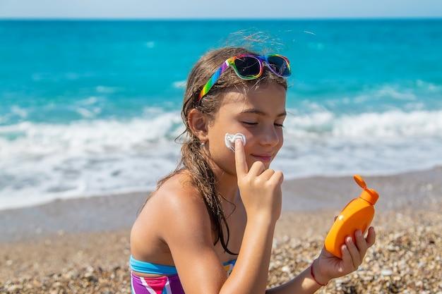 子供は顔に日焼け止めを塗っています。セレクティブフォーカス。子供。