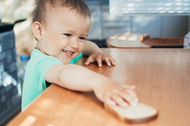Ребенок тянется к хлебу рукой