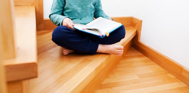 아이가 집안에 나무 계단에 앉아 종이 책을 읽고 있습니다 프리미엄 사진