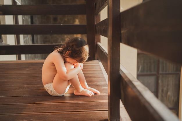 子供は悲しいことに膝を抱きしめ、白いパンティーで子供を絞って座って夏の太陽を楽しんでいます