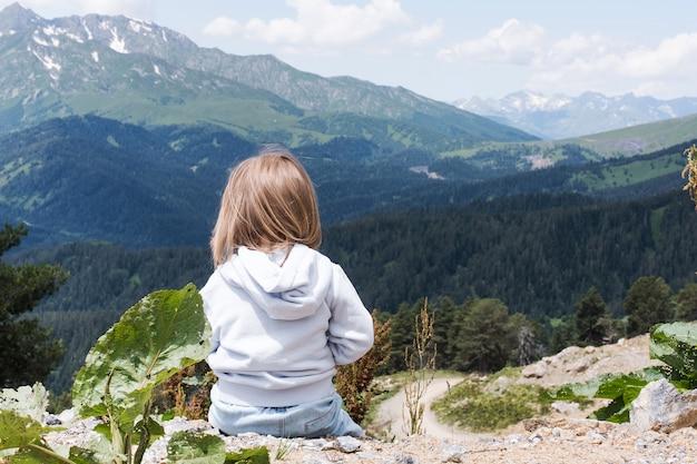 아이가 앉아서 코카서스 산맥의 풍경을 바라보고 있습니다. 야외 여행 현지 여행