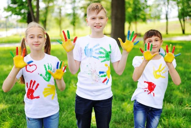 어린이는 공원에서 웃고 밝은 색의 손가락 페인트 옷으로 얼룩 져 있습니다.