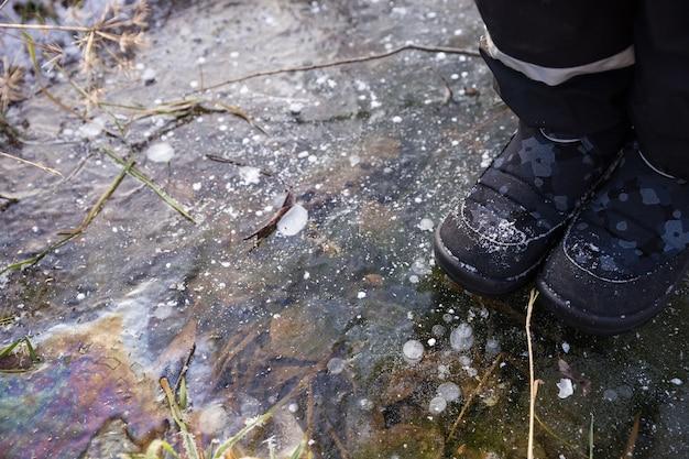 子供は葉と凍った水の下に氷の上に立っています