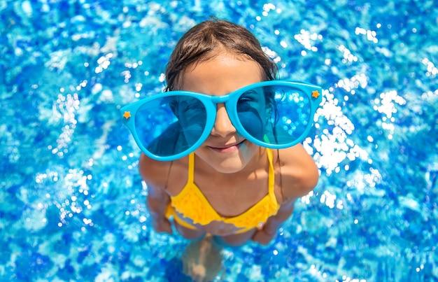 子供はプールで泳いでいます。セレクティブフォーカス。キッド。