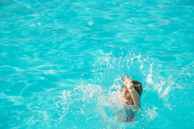 子供はプールに飛び込みます。セレクティブフォーカス。自然。