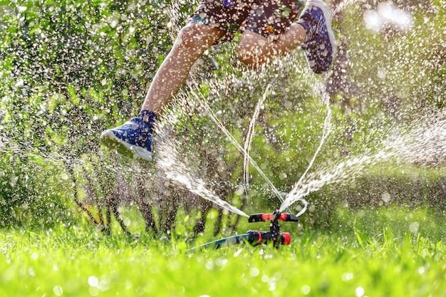 子供は庭の灌漑スプリンクラーを飛び越えます
