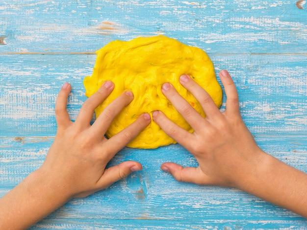 子供は青いテーブルの上で黄色いスライムの輪を指でこねます