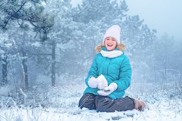 Ребенок смеется и лепит из снега. девушка в снегу. зимние забавы.