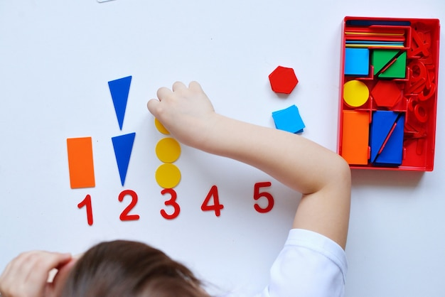 Ребенок учится числовой линии и геометрическим фигурам. дошкольник работает с монтессори материалом.